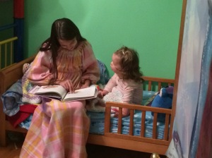 Natasha reading to Katherine in her new bed.